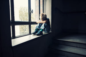 Depressed little boy in old staircase